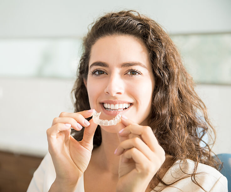 woman inserting her clear aligners on her teeth