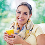 Brunette woman smiles while holding a glass of orange juice outside