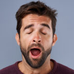 Brunette man with sleep apnea yawns because of daytime sleepiness and fatigue from poor quality sleep in Summerville