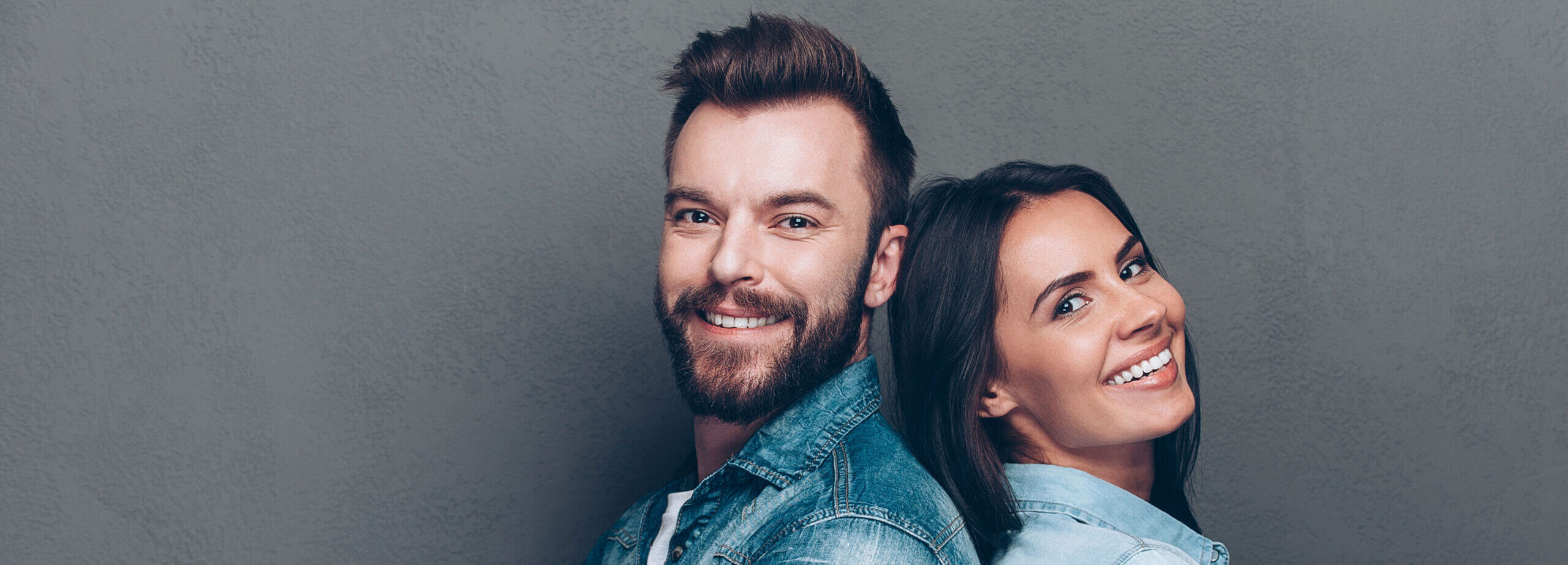 Man and woman standing back to back smiling