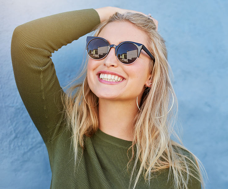 a woman wearing sunglasses smiling