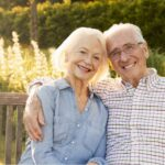 senior couple sitting on a bench hug and smile after learning about dental bridges