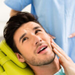 man in the dentist chair holds his jaw before a tooth extraction